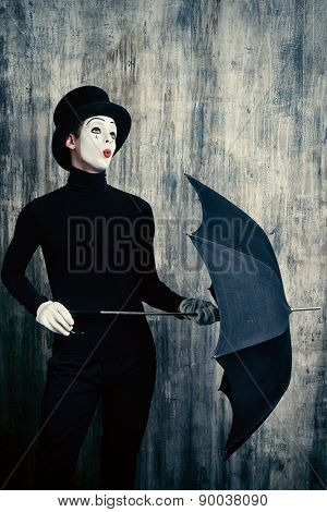 Elegant male mime artist in top hat posing with umbrella by a grunge wall.