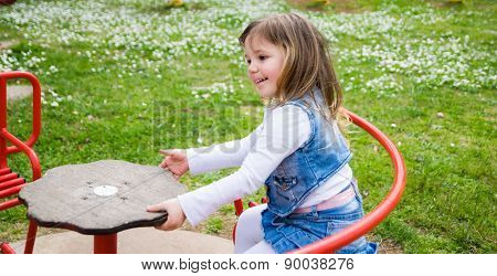 Little Girl Turns Into A Red Carousel In An Outdoor Playground