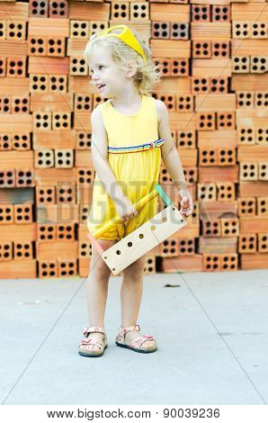 Cute Kid Playing With Construction Tools On Orange Bricks Background