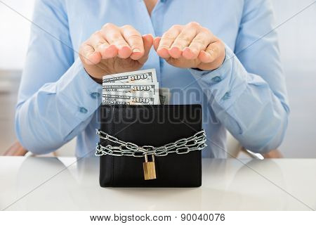 Businesswoman Saving Banknote In Wallet With Lock