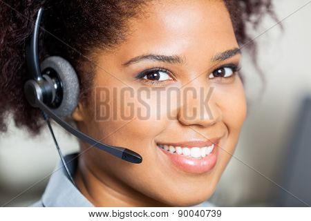 Closeup portrait of smiling female customer service representative wearing headset in office