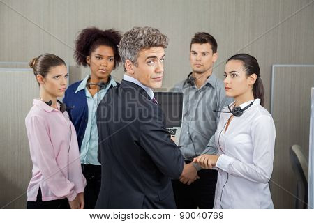 Rear view portrait of confident manager in meeting with employees at call center