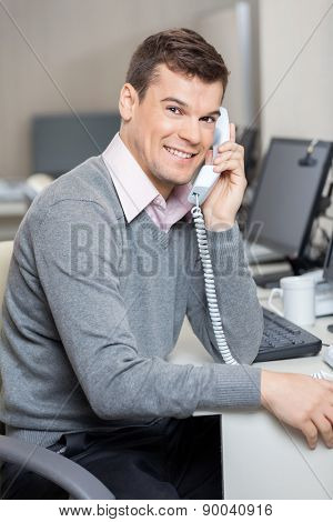 Portrait of young male customer service representative using telephone at desk in office