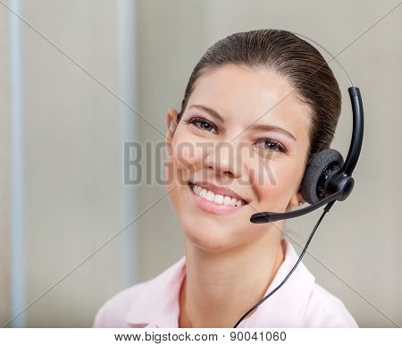 Smiling female customer support operator with headset in office