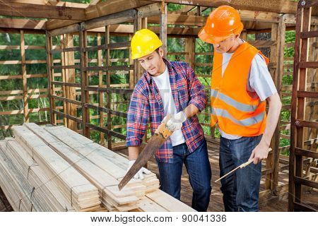 Construction workers working together in timber cabin at site
