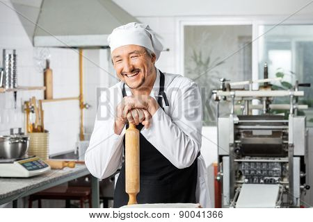 Cheerful male chef leaning on rolling pin in commercial kitchen