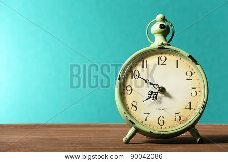 Retro clock on table on green background