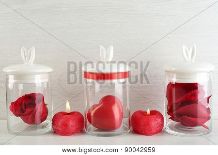 Rose flower, petals and decorative heart in glass jars on light background