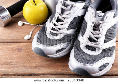 Sports shoes with dumbbell and headphones on wooden background