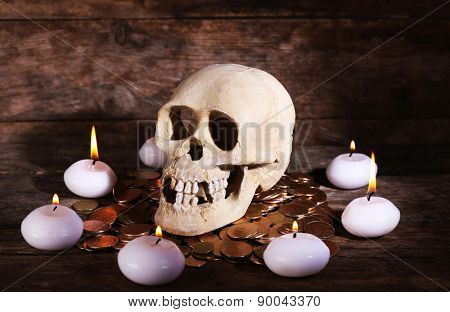 Still life with human skull, candles and gold coins on wooden background