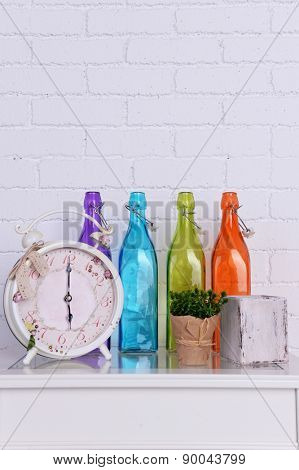 Interior design with alarm clock, plant and decorative colorful glass bottles on tabletop on white brick wall background