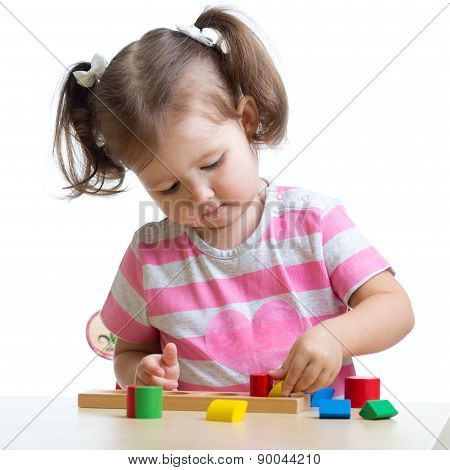 little child girl playing with puzzle toys