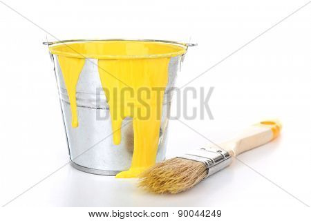 Bucket of yellow paint with brush isolated on white