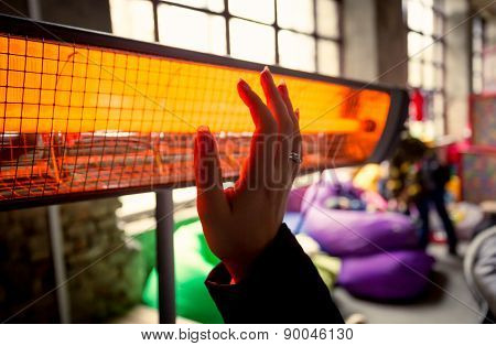 Closeup Of Woman Warming Hands At Infrared Heater