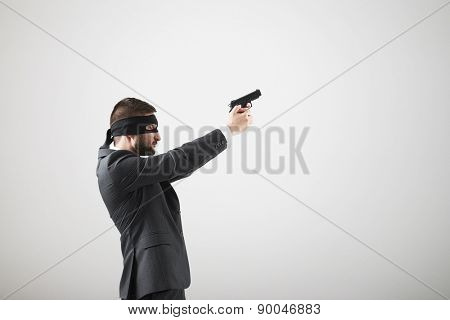 sideview of man in formal wear with gun looking up and sighting over light grey background