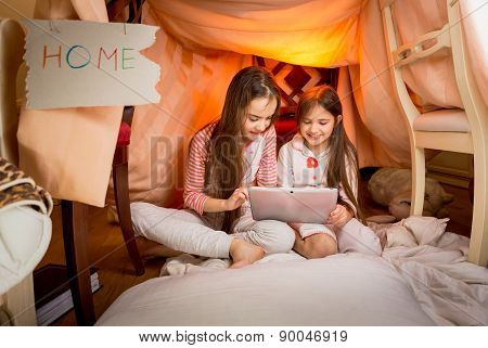 Girls Sitting In House Made Of Blankets And Using Digital Tablet