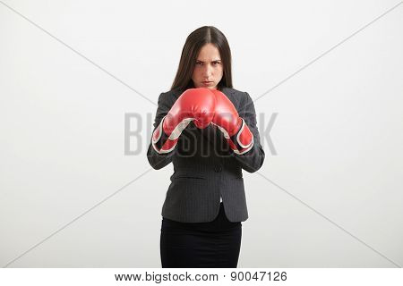 serious businesswoman in formal wear and red gloves standing in boxing pose over light background