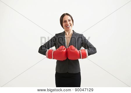 cheerful businesswoman in red boxing gloves looking at camera over light background