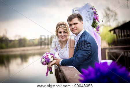 Happy Bride And Groom Posing On Pier At Lake