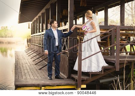 Bride And Handsome Groom Walking Down The Stairs On Pier