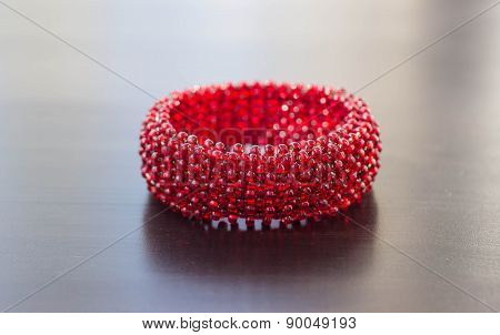 Red Bracelet From Beads Against A Dark Background