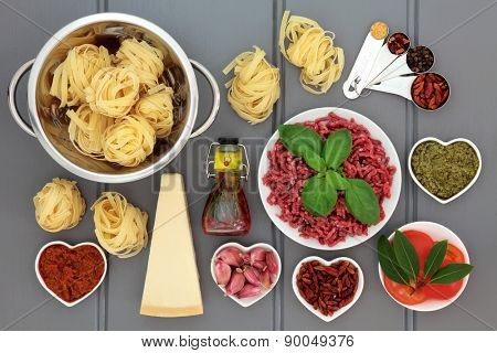 Italian food ingredients and kitchenware over grey wood background.