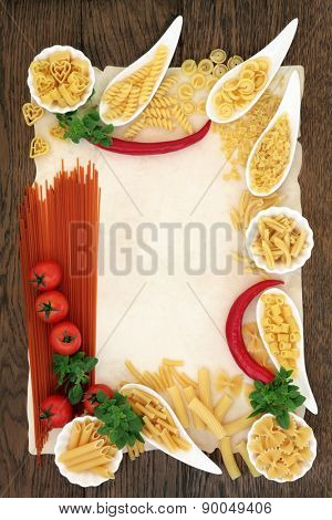 Italian pasta and mediterranean food ingredients forming an abstract border over old parchment and oak background.