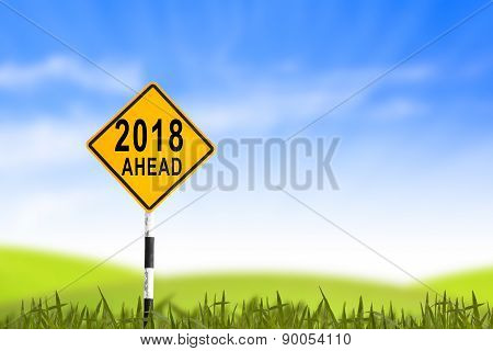 2018, Road Sign In The Grass Field To New Year And Blue Sky, Can Use As Abstract Background