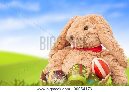 Rabbit, Sit On Green Grass And Group Of Colorful Eggs Are Behind With Blue Sky Background For Happy