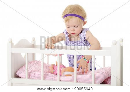 An adorable 2-year-old comforting her doll that's laying in her toy crib.  On a white background.