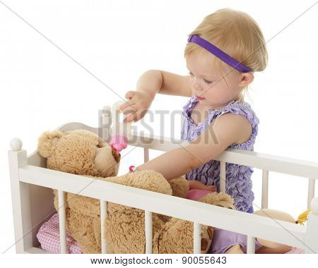 An adorable 2-year-old feeding a large stuffed bear over the railing of her doll crib.  On a white background.