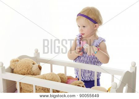 An adorable 2-year-old standing by her doll crib ready to feed her toy bear from a baby bottle.  On a white background.