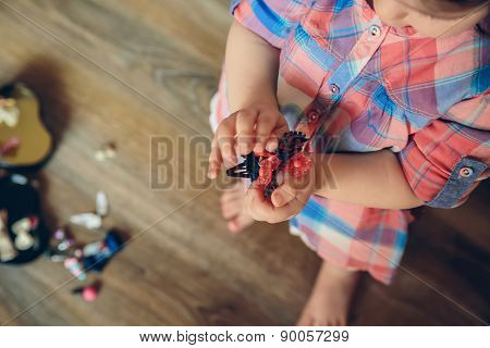 Baby girl playing with hair clips in the hands