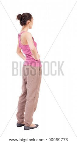 back view of standing young beautiful  woman.  girl  watching.  backside view of person.  Isolated over white background. African-American woman in brown slacks put his hands on the belt.