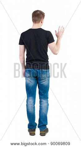 Back view of handsome man in t-shirt  greeting waving from his hands. Standing young guy in jeans. backside view of person.  Isolated over white background. guy in a vest waving uncertainly.
