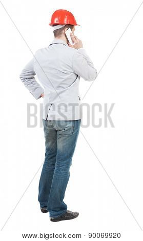 Backview of business man in construction helmet stands and enjoys tablet or using a mobile phone. Standing young guy. Rear view people collection.  backside view of person. Young businessman talks.