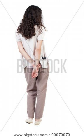 back view of standing young beautiful  woman.  girl  watching. Rear view people collection.  backside view of person. curly girl standing with one hand clasping the other behind his back.
