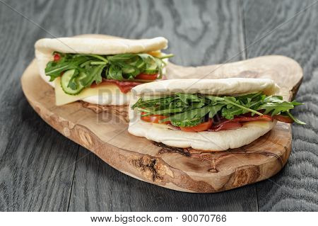 rustic sandwiches with ham arugula and tomatoes in pita bread, on wood table