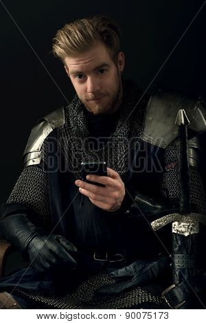 Ancient knight in metal armor holding a mobile phone in hand