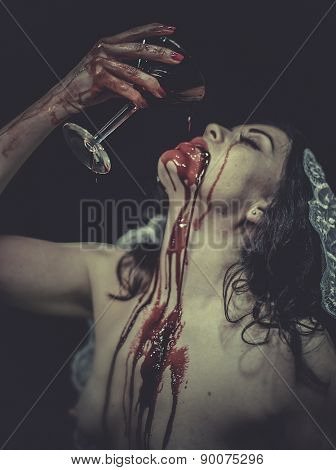 naked woman with blood on his face drinking from a cup, vampire