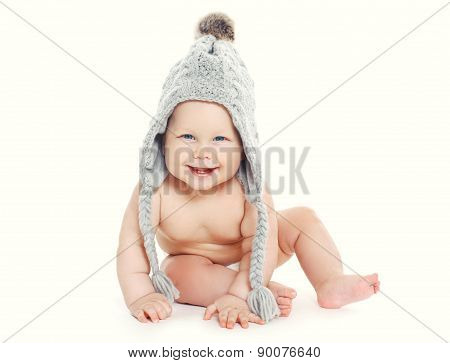 Cute Smiling Baby In Knitted Hat Sitting On A White Background