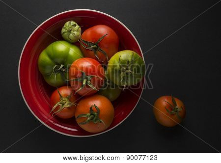 Red and green organic tomatoes in a bowl -view from top