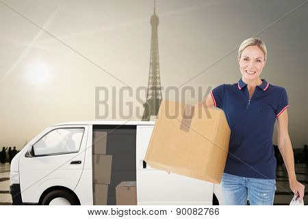 Happy delivery woman holding cardboard box and clipboard against eiffel tower