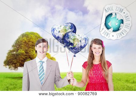 Smiling geeky couple holding red balloons against tree in green field