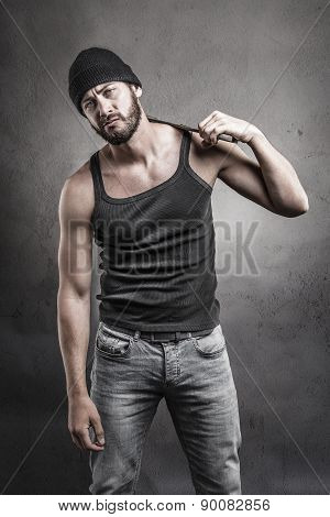 Perplexed Man Standing Holding A Wrench