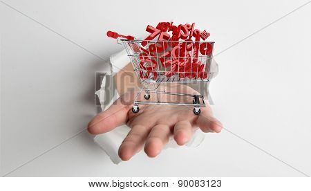 Hand bursting through paper against white background with vignette