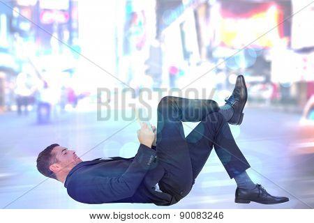 Businessman lying on the floor reading book against blurry new york street