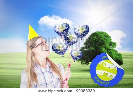 Geeky hipster holding red balloons against sunny green landscape