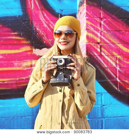 Portrait Of Stylish Smiling Girl With Old Retro Camera Having Fun Outdoors Against The Colorful Graf