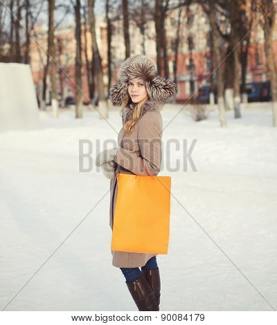 Pretty Woman Dressed A Coat And Fur Hat Walking Outdoors With Shopping Bag In The City